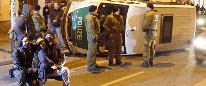 Linksextremisten posieren vor einem umgeworfenen Polizeiauto in Dresden (2009) Foto: picture alliance/dpa