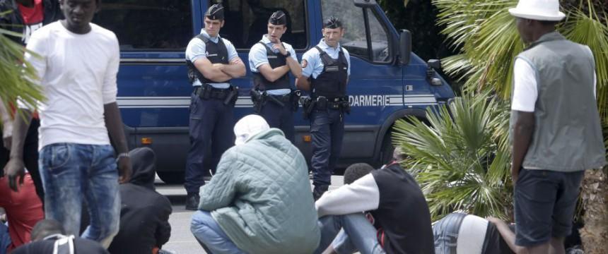 Afrikaner sitzen vor der Grenze, die von französischen Gendarmen bewacht wird Foto: Lionel Cironneau/AP/Picture Alliance