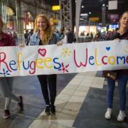 Drei Frauen begrüßen in Frankfurt am Main Asylsuchende Foto: Frank Rumpenhorst/dpa