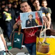 Asylbewerber in München mit einem Foto von Bundeskanzlerin Angela Merkel (CDU) Foto: picture alliance/dpa