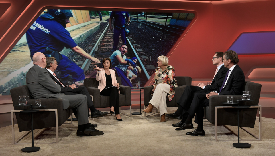 Gäste diskutieren, im Hintergrund das angebliche Gewalt-Foto