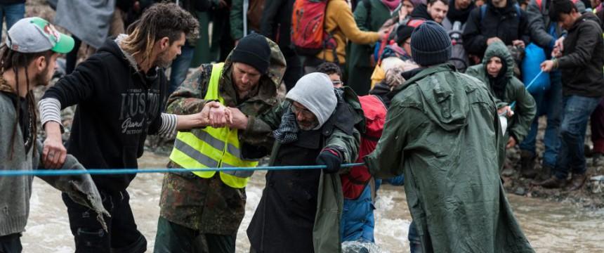 Asylaktivisten helfen Flüchtlingen bei der Flußüberquerung bei Idomeni Foto: picture alliance/Nur Photo