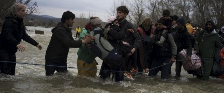 Asylaktivisten helfen Einwanderern bei der Flußüberquerung bei Idomeni Foto: picture alliance/NurPhoto