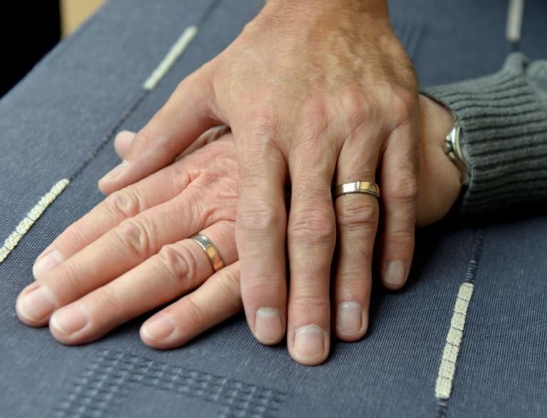 Zwei homosexuelle Männer legen die Hände übereinander