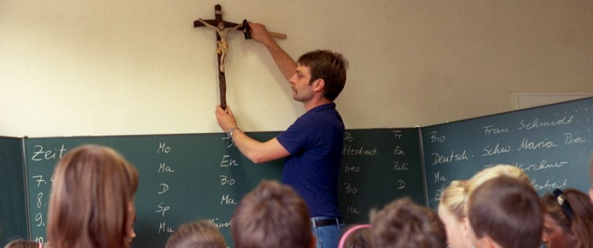 Lehrer befestigt Kreuz Foto: picture-alliance/dpa