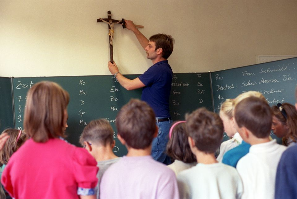 Lehrer befestigt Kreuz