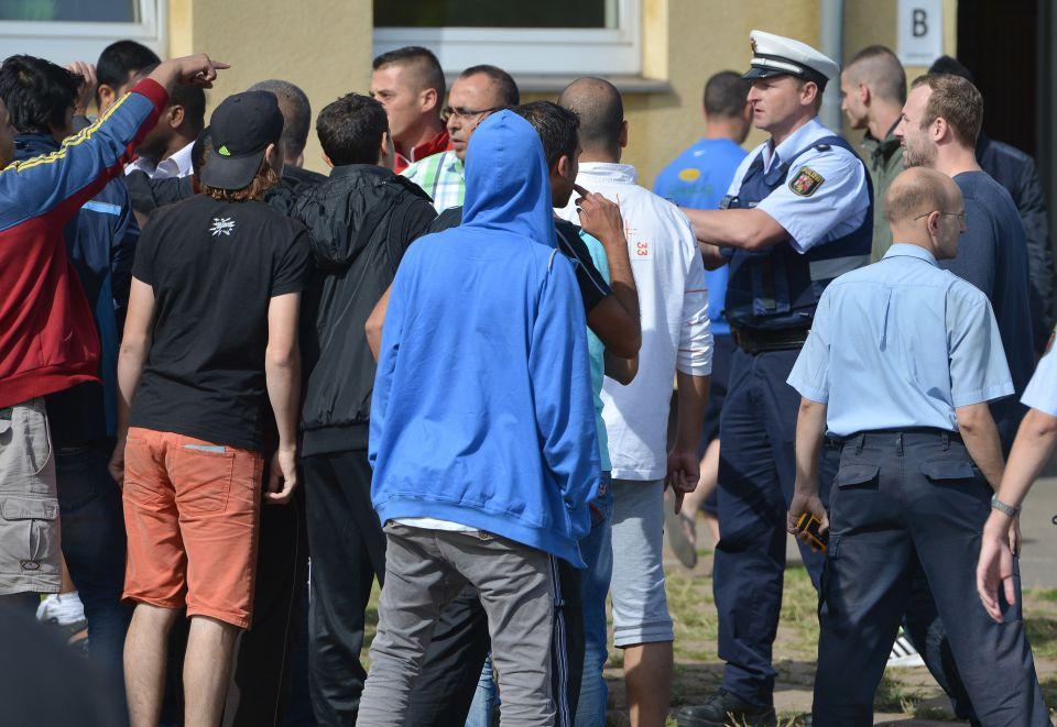 Polizist versucht Asylsuchende zu beruhigen