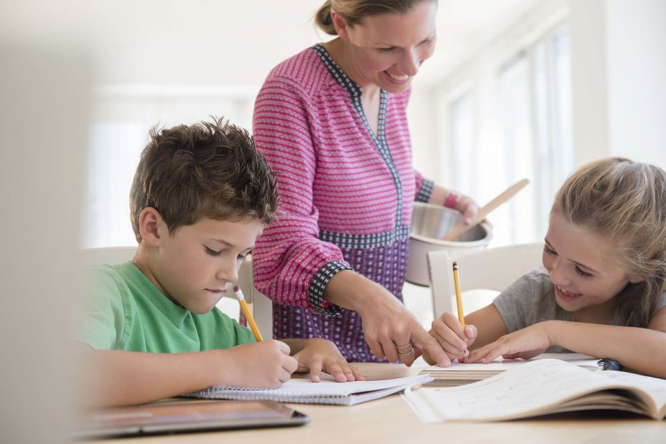 Mutter hilft Kindern bei Hausaufgaben