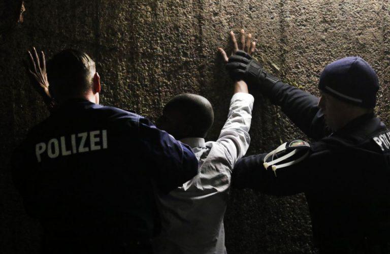 Polizisten durchsuchen Mann nahc Drogen