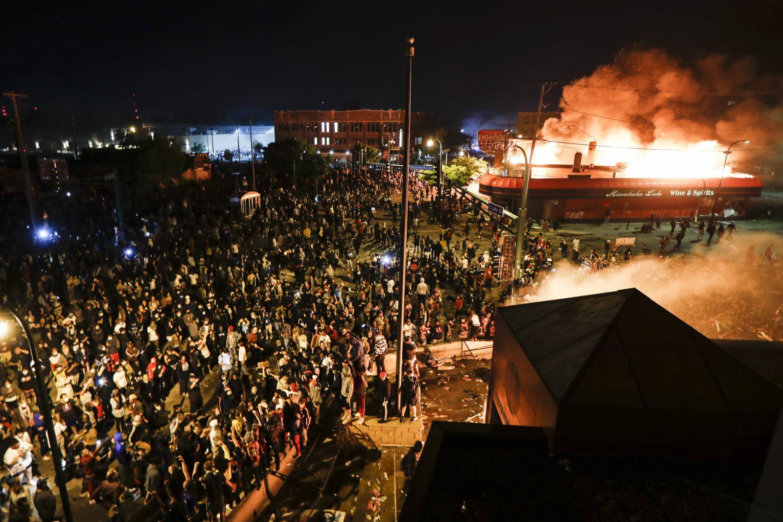 Eine Polizeiwache (rechts unten) und ein Schnapsladen gehen in Minneapolis während der Unruhen in Flammen auf Foto: picture alliance / AP Photo