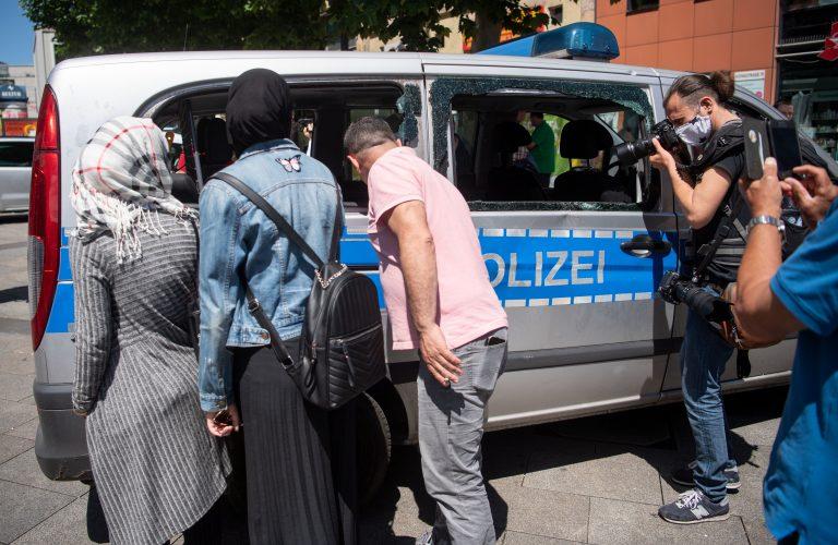 Passanten und Journalisten betrachten einen zerstörten Polizeiwagen nach den Stuttgarter Ausschreitungen Foto: picture alliance/Marijan Murat/dpa
