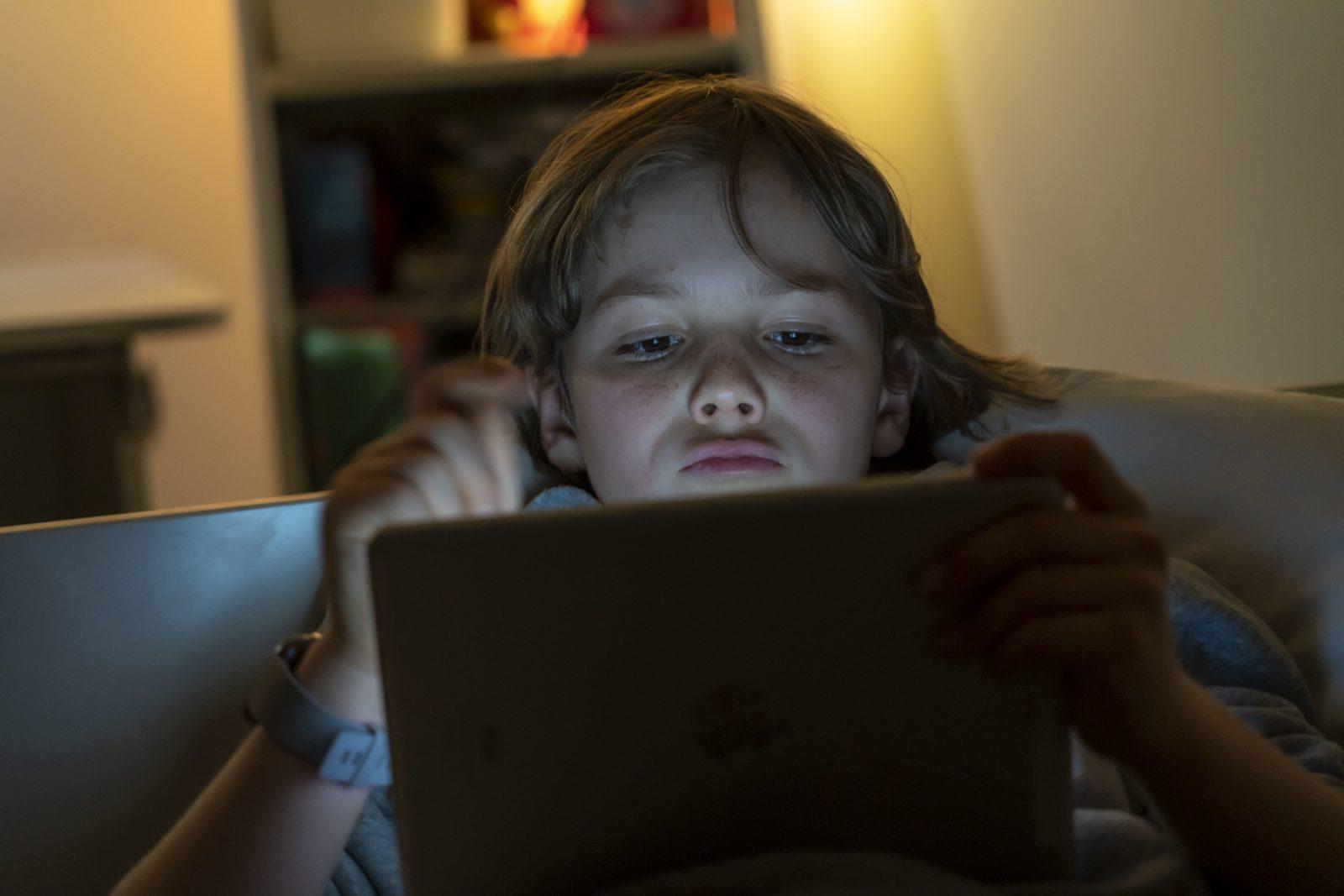 Ein Junge spielt Computerspiele an einem Tablett PC.