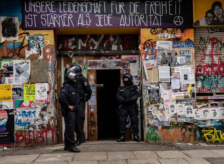 Polizisten stehen am Eingang eines Hauses in der Rigaer Straße Foto: picture alliance/Paul Zinken/dpa