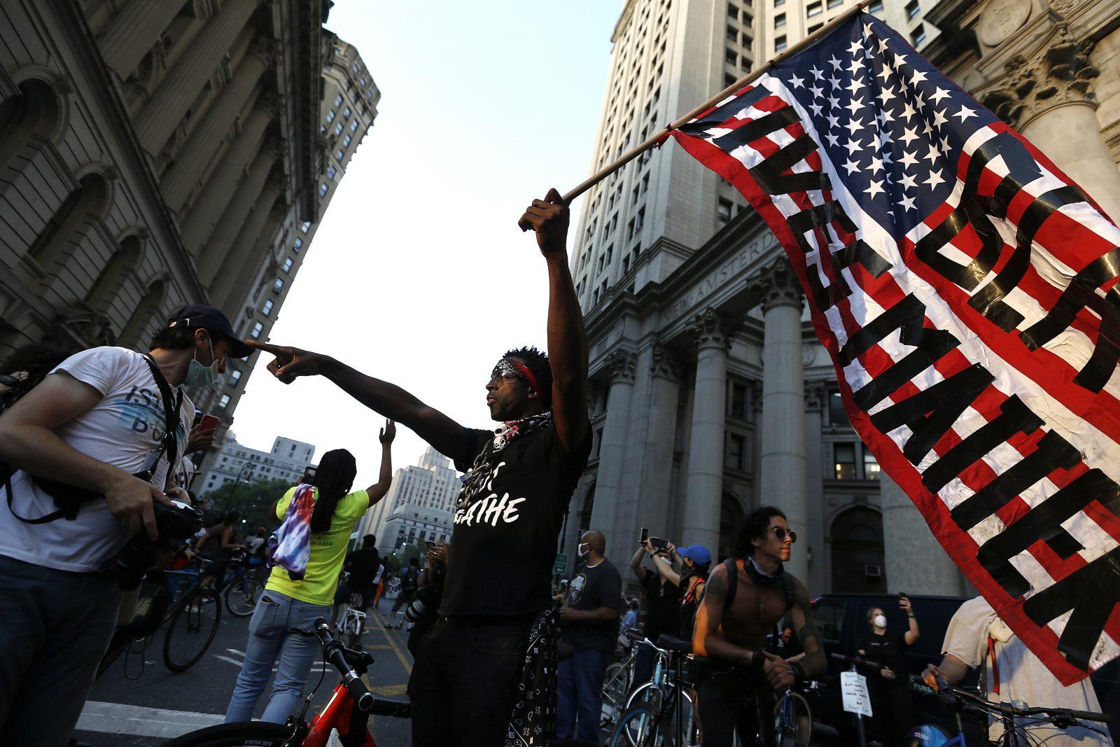 """Ein Demonstrant hält in New York eine USA-Flagge in die Höhe mit dem Schriftzug """"Black Lives Matter""""."""