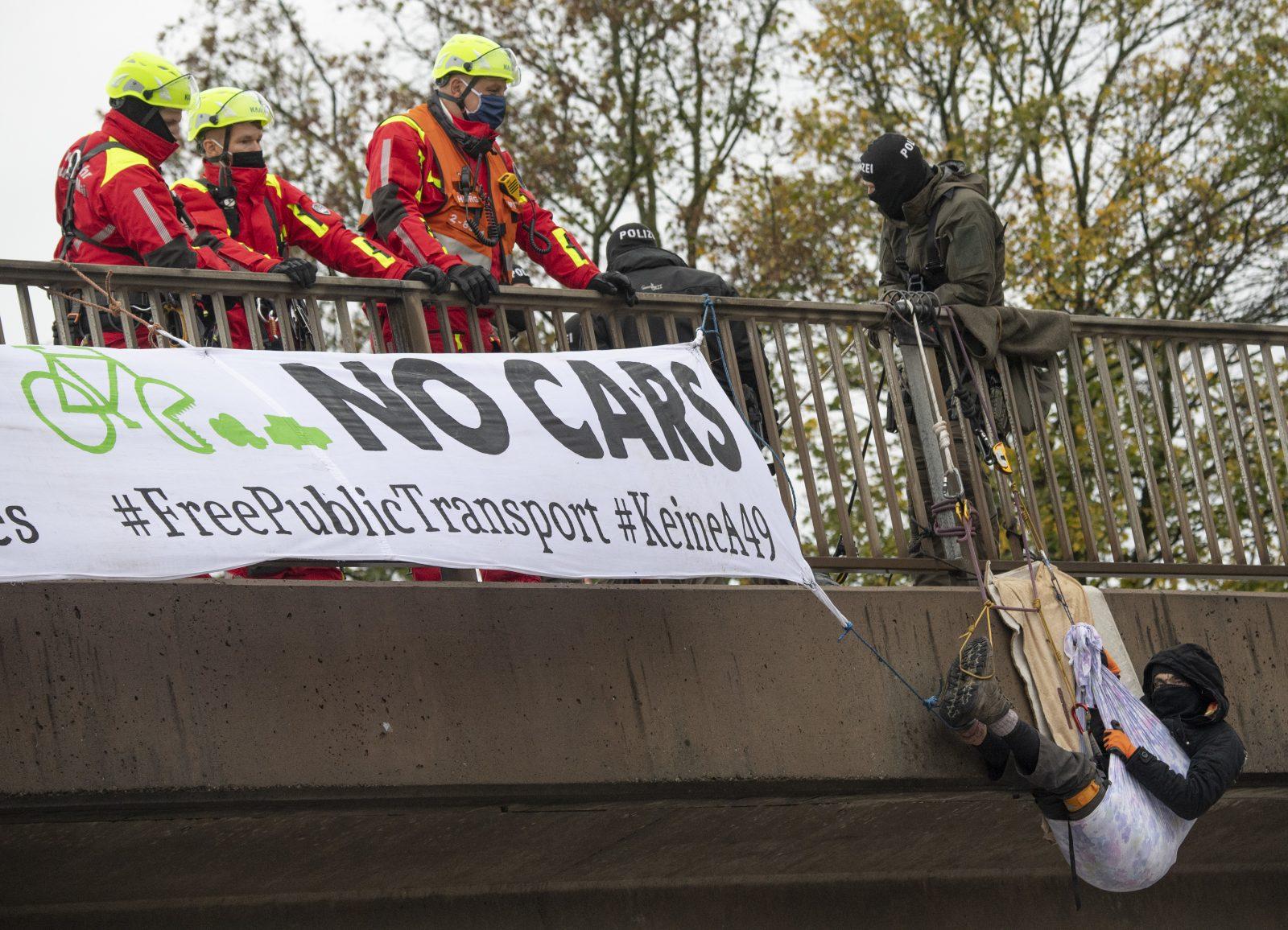 Einer der Umweltschützer hängt an der Autobahnbrücke über der A5 am Frankfurter Flughafen Foto: picture alliance/Boris Roessler/dpa