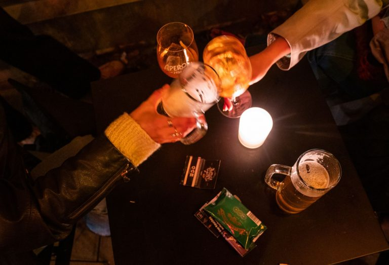 Anstoßen vor der Corona-Sperrstunde: Zwei Gäste prosten sich in einer Bar in Neukölln zu