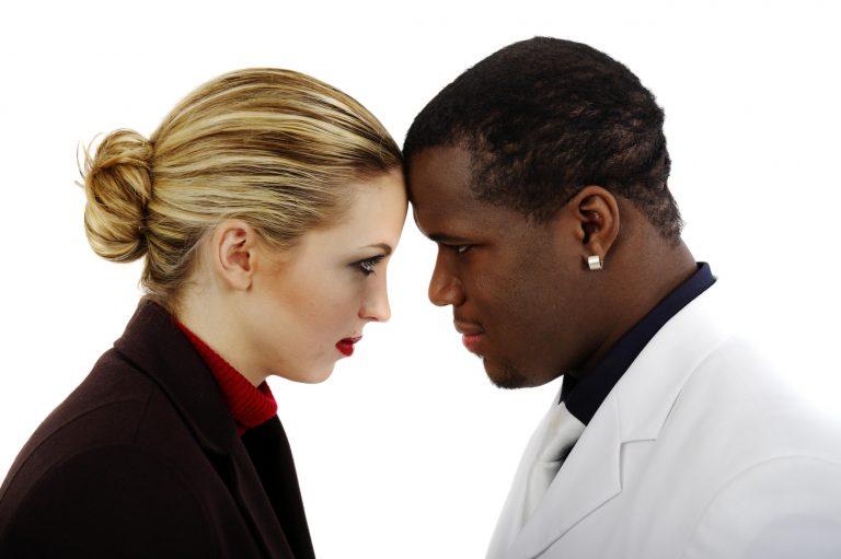 Ein schwarzer Mann und eine weiße Frau stehen Kopf an Kopf.