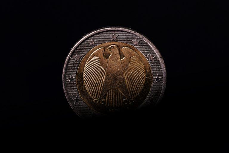 Eine 2-Euro-Münze, halb im Schatten.