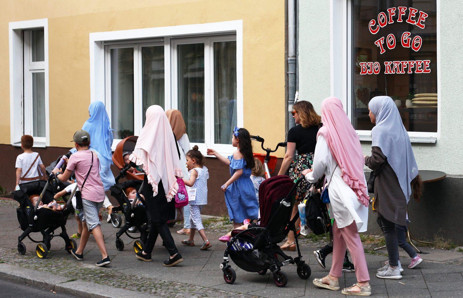 Moslemische Frauen gehen zusammen mit Kindern neben einer deutschen Frau über einen Fußweg in Schöneberg.