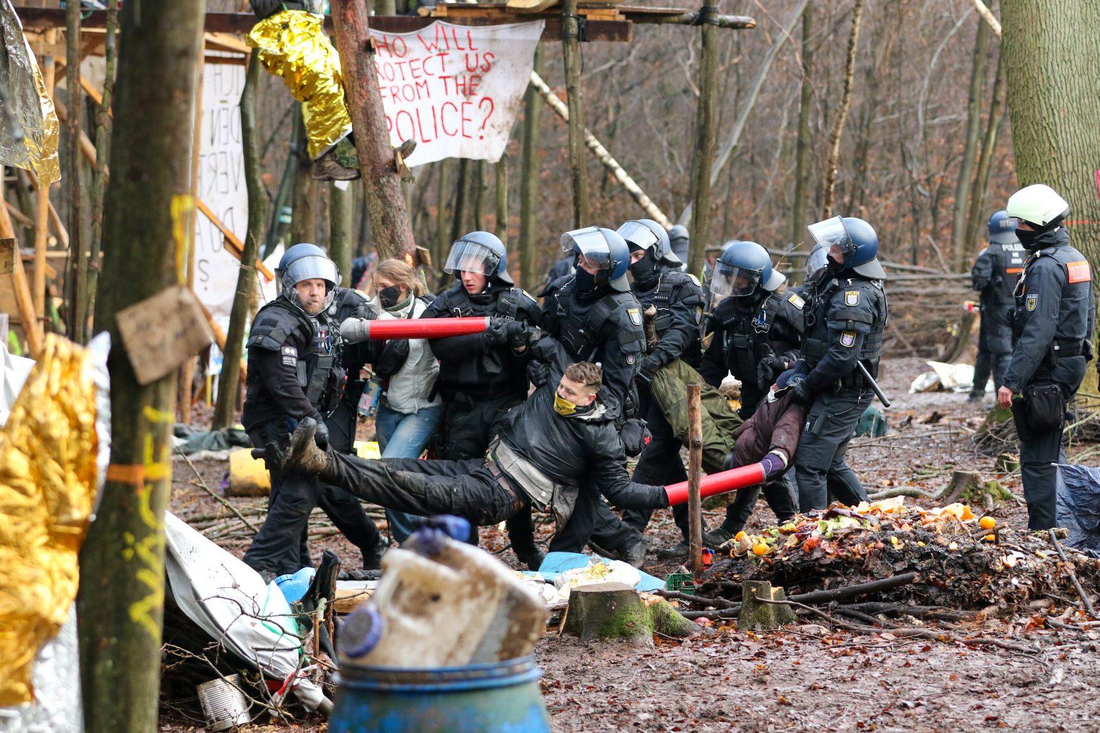 Polizisten tragen mehrere Waldbesetzer im Dannenröder Forst weg, die sich aneinander gekettet haben Foto: picture alliance/dpa | Nadine Weigel