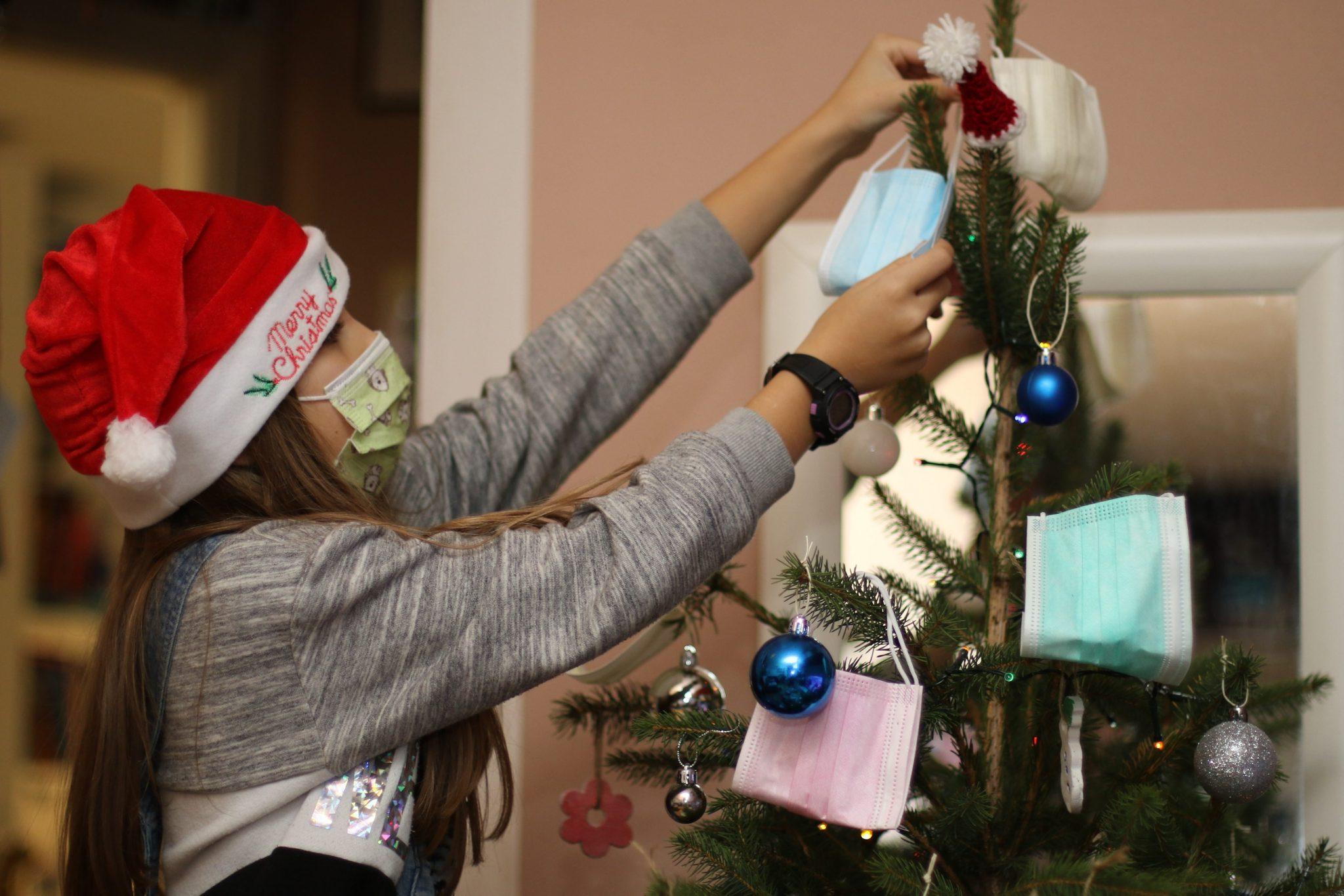 Ein Mädchen schmückt den Weihnachtsbaum mit Mundschutzmasken.